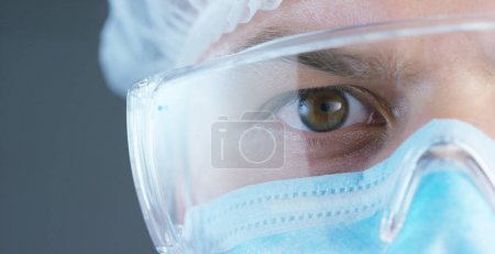 A portrait of a doctor or surgeon in a medical mask, a respirator, brown eyes, a surgical cap, in a hospital or a clinic.