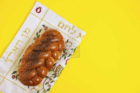 Shabbat shalom, challah on a napkin and yellow background. Not isolated, copy space, authors processing.