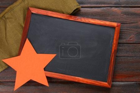 Photo for Chalkboard with empty space, military cap and red star on a wooden table. Day of the defender of the fatherland and May 9 - Royalty Free Image