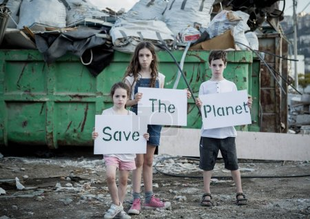Save the planet. young kids holding signs standing in a huge junkyard