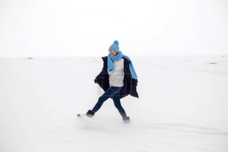 girl running in a snowy field in a jacket