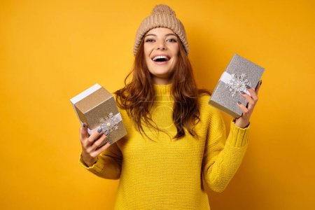 Photo for A brunette is standing on a yellow background in a yellow sweater and hat, laughing, looking into the frame, holding gift boxes in her hands. Horizontal photo - Royalty Free Image