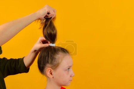 Photo pour Maman fait les cheveux de sa fille en tressant ses cheveux dans des tresses et une queue - image libre de droit