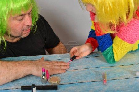 Photo pour Fille et père en perruques colorées, l'enfant peint les ongles de son père avec du vernis à ongles.. - image libre de droit