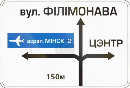 Belarusian direction road sign with directions to airport. The words mean Airport Minsk-2 (left), Filimonov Street (top) and center (right)