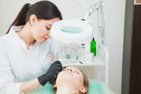 Beautician cosmetologist applying permanent makeup