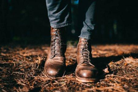 Photo pour Bizarre bûcheron en cuir brut vintage hipster masculin debout dans la forêt d'automne sur le sol avec des aiguilles d'épinette orange sèche. Couleurs d'automne et concept d'humeur. Journée ensoleillée en plein air le week-end - image libre de droit