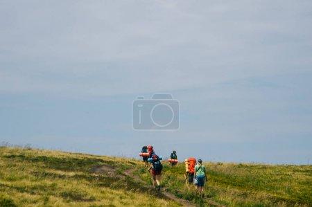 Photo pour Groupe de voyageurs marchant sur la route de montagne - image libre de droit
