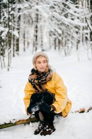 Photo pour Étrange femelle bizarre allongée sur un arbre dans une forêt enneigée d'hiver. Belle jeune fille charmante détente en plein air. Femme inhabituelle en vacances reposant sur la nature. Dame solitaire voyageant par temps froid glacial jour - image libre de droit