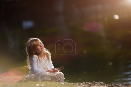 A sweet little girl sitting with chicks on the bri...