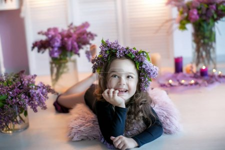 Little smiling girl posing lying on floor with purple flowers bouquets