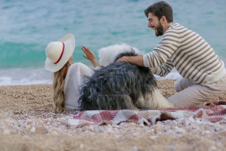 young woman in straw hat and bearded man playing with fluffy dog sitting on plaid on sea shore