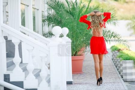 attractive blonde woman in red dress and sunglasses posing outdoors, back view