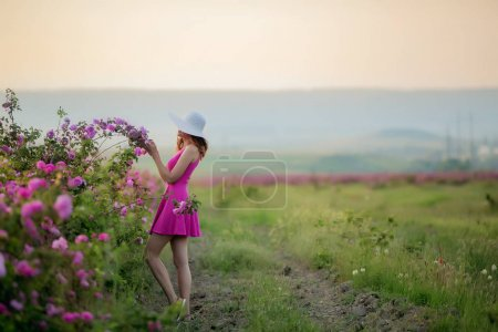 full length of young woman in straw hat and dress posing with purple flowers