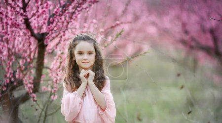 beautiful little girl posing outdoor in the garden against blossoming trees