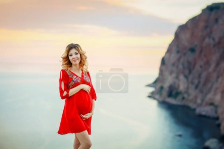 Photo for Beautiful pregnant woman posing outdoors against amazing nature landscape wearing red dress - Royalty Free Image