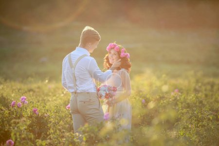 young beautiful couple on outdoor wedding photosession posing on the field