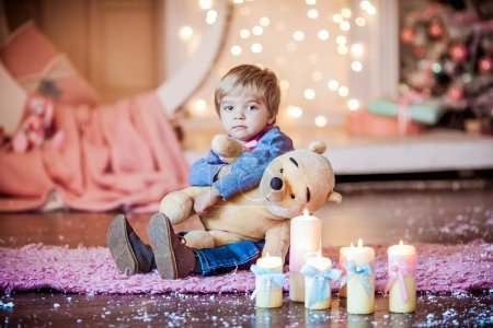 Photo for A little boy is photographed in the new year holiday on the background of a Christmas tree and Christmas candles. - Royalty Free Image