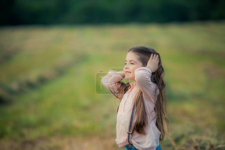 Photo for Close up of a child in a pink blouse with long dark hair in an open field. - Royalty Free Image