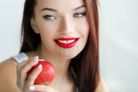 Photo for Beautiful woman with stage makeup in a white T-shirt closeup holds fresh fruits in her hands. - Royalty Free Image