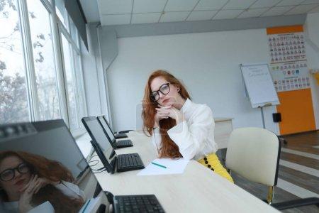 Photo pour Une femme s'assoit à une table devant un ordinateur et élabore des idées d'affaires. - image libre de droit