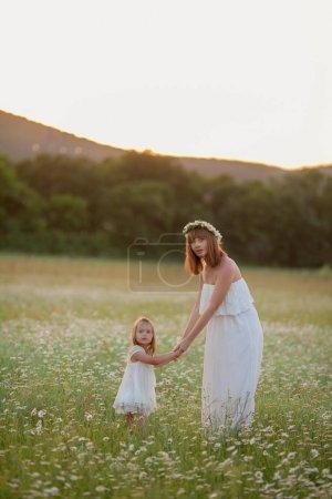 Photo pour Femme en plein air heureux au coucher du soleil jouer avec bébé fille . - image libre de droit