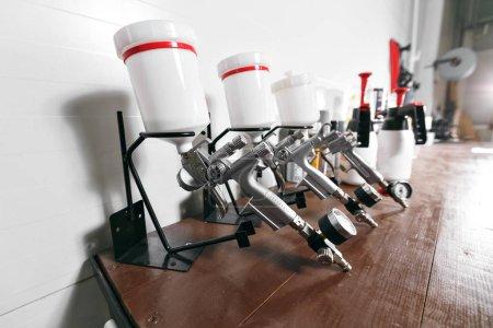 Photo pour Pistolet de pulvérisation sur la table en bois. au service de l'automobile. utilisé pour le revêtement et peinture industrielle. - image libre de droit