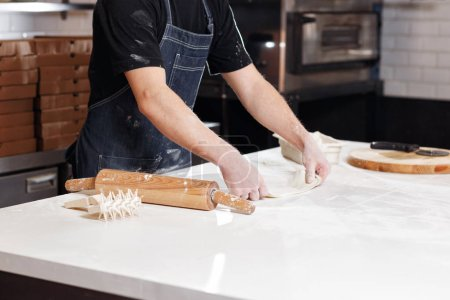 Roll out the dough. Closeup hand of chef baker in ...