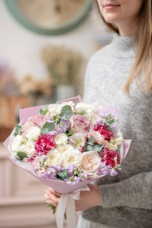 Photo for Beautiful bouquets of mixed flowers in womans hands. the work of the florist at a flower shop. Fresh cut flower - Royalty Free Image