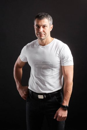 Photo for Handsome Athletic man in white blank t-shirt standing on black wall background. - Royalty Free Image