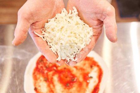 Photo pour Pizza à cuire. arrange les ingrédients du fromage sur la préforme de pâte. Closeup main du chef boulanger en uniforme tablier blanc cuisinier à la cuisine. - image libre de droit