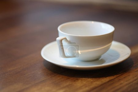 Photo for Empty cup, ceramic saucer, drink and food, non-alcoholic beverage, wood table, isolated subject, good morning, white cup, close up - Royalty Free Image