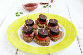 Sandwiches with black rye bread in the shape of a heart, blood sausage (Morcillo) and pieces of sweet pepper on skewers and tomato sauce, on a white wooden background.