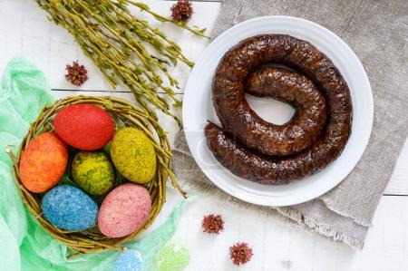 Easter dishes: colorful colored eggs, home-made sausage ring, willow twigs on a light wooden background. Top view.
