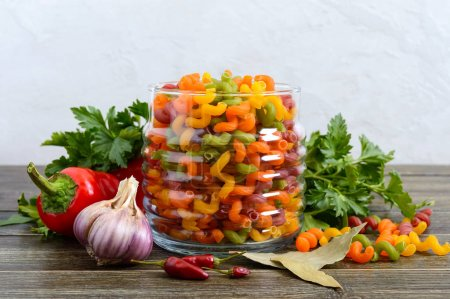 Cavatappi colored raw pasta in a glass jar, fresh vegetables, greens on a wooden background. Pasta colorata. Pasta with vegetables. Elbow macaroni