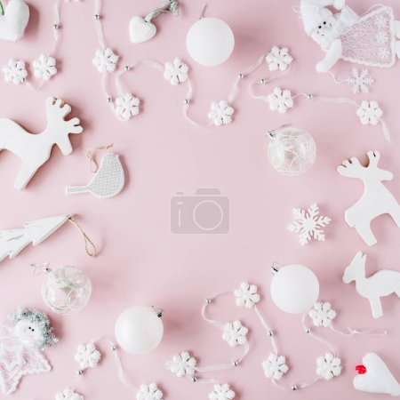 Photo for Frame made of white christmas decorations with christmas glass balls, tinsel, bow, elk, bird on pink background. christmas wallpaper. flat lay, top view - Royalty Free Image