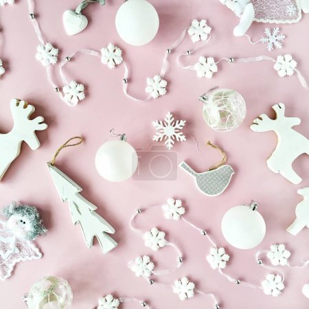 Photo for Pattern made of white christmas decoration with christmas glass balls, tinsel, bow, elk, bird on pink background. christmas wallpaper. flat lay, top view - Royalty Free Image