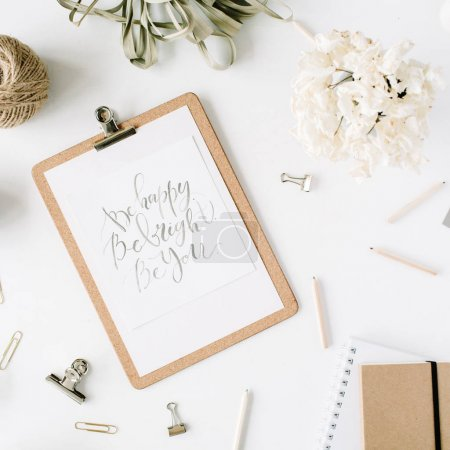 Photo for Flat lay, top view office table desk. feminine desk workspace with clipboard and inspirational quote, twine, pencils, floral bouquet, craft diary and clips on white background. - Royalty Free Image