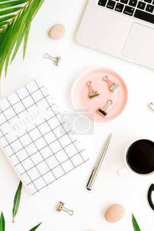 Photo for Flat lay, top view office table desk. Workspace with notebook, laptop, palm branch, coffee cup, scissors and clips on white background. - Royalty Free Image