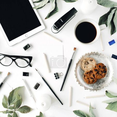 Workspace with tablet, glasses, cup of black coffee