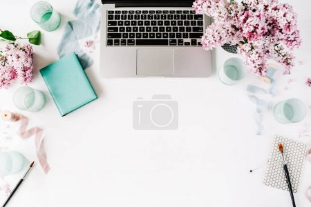 Workspace with paintbrush, laptop, lilac flowers bouquet