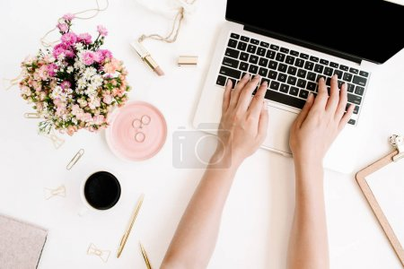 Photo for Top view office desk. Workspace with girl's hands, laptop, wildflowers bouquet, coffee cup, golden pen and clips, clipboard. Flat lay - Royalty Free Image