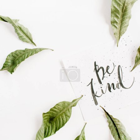 Photo for Minimalistic composition with words Be Kind written in calligraphic style on paper with leaf frame on white background. Flat lay, top view - Royalty Free Image