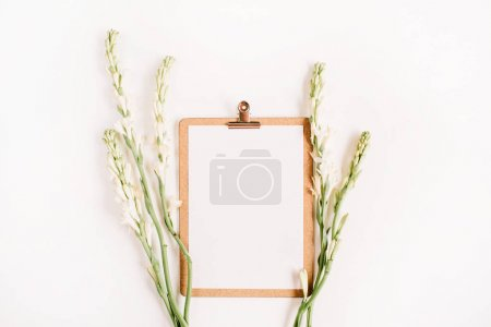 Photo for Clipboard and white flowers. Flat lay, top view. Flower background. - Royalty Free Image