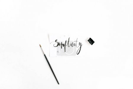 Photo for Minimalistic stylish composition with word Simplicity written in calligraphic style on paper with paint brush on white background. Flat lay, top view - Royalty Free Image
