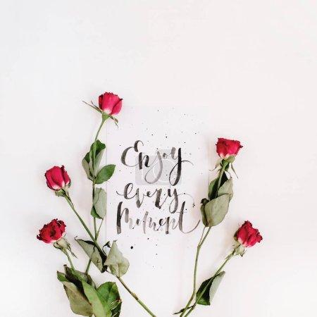 """Foto de Inspiracional """"Disfrutar cada momento"""" escrito en estilo caligráfico en papel con rosas rojas aisladas sobre fondo blanco. Vista plana endecha, superior - Imagen libre de derechos"""