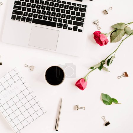 Photo for Workspace with laptop, red roses flowers, coffee cup, notebook and clips on white background. Flat lay, top view. Feminine background. - Royalty Free Image