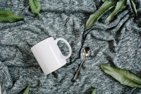 Photo for Blank template of white mug, spoon and green leaves on grey textile background. Flat lay, top view. - Royalty Free Image