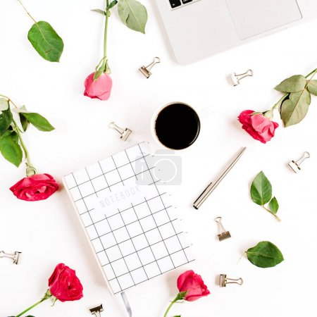 Workspace with laptop, red roses flowers, coffee cup, notebook