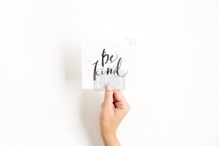 Photo for Minimal pale composition with girl's hand holding card with quote Be Kind written in calligraphic style on paper on white background. Flat lay, top view - Royalty Free Image